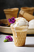 Homemade vanilla ice cream in small waffle cup served with purple edible flowers