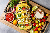 Variety of vegetarian corn tacos with vegetables, green salad, chili pepper