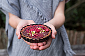 Spiced Chocolate Tarts being held in a girl's hands