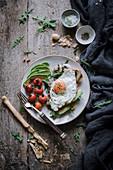 Brotscheibe belegt mit Spiegelei, Avocado und Pilzen zum Brunch