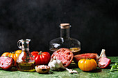 Still life with variety of red and yellow organic tomatoes with olive oil, garlic, salt for salad over green table with black background
