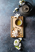 Traditional ceramic cup of hot green tea on wooden board with black iron teapot, spring flowers white magnolia and cherry blooming branches