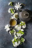 Traditional ceramic cup of hot green tea with black iron teapot, spring flowers white magnolia and cherry blooming branches
