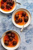 Three bowls of stewed red plums in syrup with spoons on a blue textured background