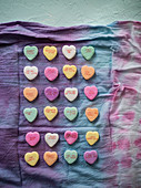 Colorful, overhead image of conversation love hearts organized on a rainbow linen on a mint green surface