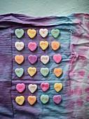 Bunte Konfekt-Herzen mit Liebessprüchen auf gefärbtem Tuch