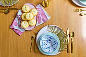 Gedeckter Tisch mit verschiedenem Geschirr und goldenem Besteck