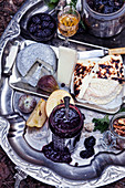 Various cheeses, jam and fruit on vintage silver tray