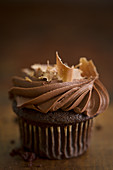 A chocolate cupcake with a cream topping and chocolate shavings