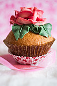 A cupcake decorated with a large sugar rose