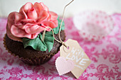 A cupcake decorated with a large sugar rose and a gift tag