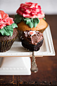 Cupcakes decorated with large sugar roses on a cake stand and a chocolate cupcake