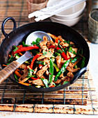 Chicken with mangetouts, peppers, zucchini and cilantro in a wok (Thailand)