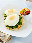Two soft eggs on a pita with spinach and tomato salad
