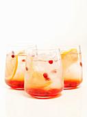 Drei Getränke mit Granatapfelkernen und Zitronenscheiben auf weißem Untergrund
