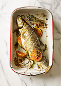 Whole fish wrapped in twine with citrus fruit in a baking pan