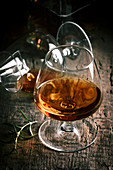 Glass of cognac on old oak wooden table