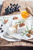 Brie, angeschnitten serviert mit Honig, Nüssen, Rosmarin und Trauben