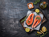 Two fresh raw salmon steaks on paper with salt, peppers, lemon, and rosemary