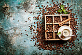 Coffee beans in old wooden box, cup of fresh making coffee