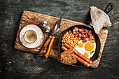 English Breakfast: Würste, Bacon, Spiegelei, Baked Beans, Brot und Kaffee