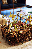 Spring flowers in DIY basket made from twigs
