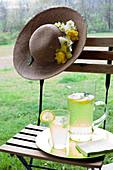 Zitronenlimonade auf Gartenstuhl und Sommerhut mit Blütendeko