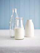 Milch in Glasflasche und leere Behälter
