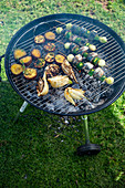 Fish skewers, potatoes and fennel on a grill