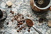 Top down view of scattered coffee beans, ground coffee in a spoon, brewed coffee in jezva on a granite surface