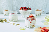 Lime and strawberry posset with streusel in glass jars on a white background