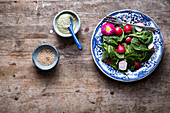 Salad with radish and spinach with a dressing and sesame seeds on a wooden table and a blue bowl