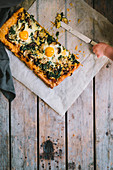 Pizza with spinach, fried eggs, courgette, melted cheese and a small child hand