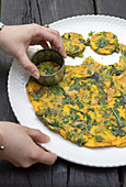 Mini herb omelettes being cut out