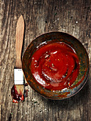 Barbecue sauce and a brush on a wooden background
