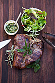 Grilled T-bone steak with salsa verde and a wild herb salad