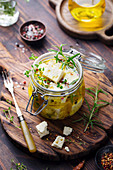 Feta cheese marinated in olive oil with fresh herbs in glass jar