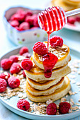 A stack of pancakes with raspberries and raspberry sauce