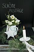 Rustikale Weihnachtsdeko mit Kerze und Christrosen