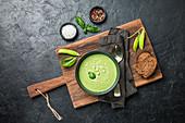 Broccolicremesuppe mit Erbsen serviert in Schale mit Brot auf Holzbrett