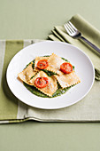 Burrata ravioli on basil pesto with cherry tomato confit