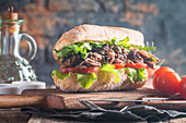 Beef sandwich with tomato and salad on wooden cutting board with ingredients