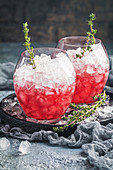 Red summer cocktail with berry, ice and thyme