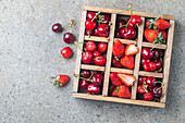 Frische Beeren und Kirschen im Setzkasten