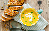 Yellow cream of pea soup with green peas in a soup cup