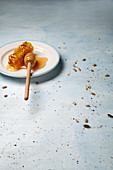 A honeycomb with a honey dipper on a plate