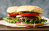 Grilled burgers with tomato, cheese, onion, cucumber and lettuce leaves