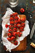 Baked cherry tomatoes on a sheet of baking paper