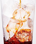 Dark brown liquid being poured on to ice in a clear glass