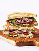 Toasted sandwich with roast beef, onions, tomato, spring mix, mayonaise on a cutting board